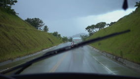 The view from the car window on the way during the rain amongst the green mountains stock video