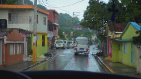 The view from the car window at the wet streets in the rain. The view from the car window at the wet streets and houses in the rain stock footage
