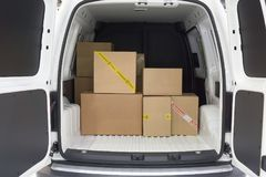 In the cargo area of the truck. View of the cargo area of light commercial vehicle. Russian text on yellow adhesive tape of the box: First class mail. Russian royalty free stock photos