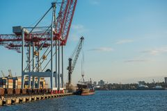 A view of the cargo port and cranes,. A ship with containers at the pier. Sunny day, calm water of the sea.  Ukraine. Black Sea Stock Images