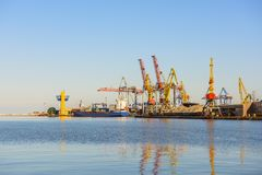 A view of the cargo port and cranes,. A ship with containers at the pier. Sunny day, calm water of the sea. Odessa. Ukraine. Black Sea Royalty Free Stock Image
