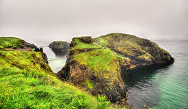 View of Carrick Island with Carrick-a-Rede Rope Bridge - Norther Stock Photos