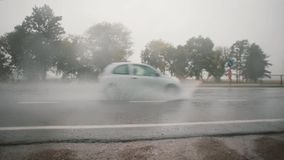 A view of cars passing by on the road in the rain, splashing water around. Trees on the other side. stock footage