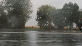 View of cars passing by on the road in the rain, splashing water around. Trees on the other side. stock video footage