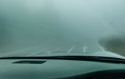 View through the cars windshield in the winter fog on the road royalty free stock image