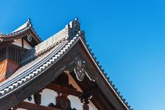 View of the carved wooden roof of the building, Kyoto, Japan. Copy space for text. Isolated on blue background. stock image