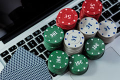 View of casino chips, cards on laptop to play online. Royalty Free Stock Images