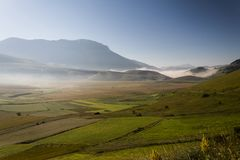 View of Castelluccio di Norcia Umbria at dawn, with mist, big meadows and totally empty blue sky.  Royalty Free Stock Photo
