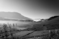 View of Castelluccio di Norcia Umbria at dawn, with mist, big meadows and totally empty sky.  Stock Photos