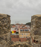 A view from the Castelo de S. Jorge, Lisbon, Portugal. There are some red-tiled roof tops visible in the distance below the wall of the castle as well as a Stock Photography