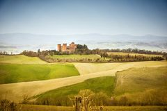 View of Castle of Gallico. Beautiful landscape of hills and fields near Asciano in Tuscany, Siena, Italy. The Castello di Gallico, with its five stone and red royalty free stock photography