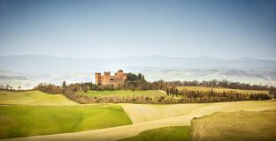 View of Castle of Gallico. Beautiful landscape of hills and fields near Asciano in Tuscany, Siena, Italy. The Castello di Gallico, with its five stone and red stock image
