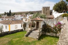 View of the castle wall and tiled roofs in Obidos, Portugal. There is a nice porch and a door in the foreground Stock Image