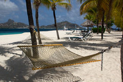View of Casuarina Beach on Palm Island, Saint Vincent and the Grenadines. Hammock view of Casuarina Beach with sun loungers, pagoda, Hobby Cats, palm tree Royalty Free Stock Photography
