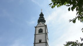 View of the cathedral bell tower of Klagenfurt. View the whole reflection of the cathedral bell tower in the glasses of a building Klagenfurt stock video