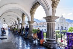 View of cathedral from city hall terrace, Antigua, Guatemala. Antigua, Guatemala - April 10, 2019: View of San José cathedral & central park through arches on stock image