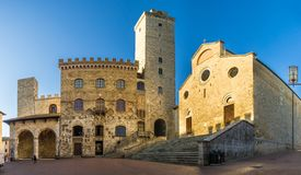 View at the Cathedral of Santa Maria Assunta with Town hall building at the Place of Duomo in San Gimignano, Italy royalty free stock photos