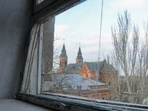 View of the Catholic Church from the window, Mykolaiv, Ukraine. The view from a broken window of Saint Joseph Roman Catholic Church with towers in Mykolaiv City Royalty Free Stock Image