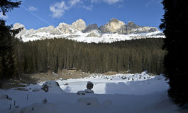 View of Catinaccio - Dolomites. Snowy landscape and Carezza icy lake in the Dolomites royalty free stock photo