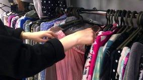 View Of Caucasian Teenage Girl Choosing Clothes In A Second Hand Shop. View Of Caucasian Teenage Girl Choosing Clothes In A Second Hand Shop stock footage