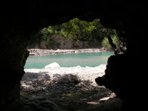 View from a cave. Big cave with a beautiful view of the lake formed by the mountain river in a canyon Geynyuk Stock Photo