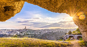 View through cave of sassi di Matera,basilicata, Italy, UNESCO under blue sky and sun flare. Panoramic view through cave of sassi di Matera,basilicata, Italy Stock Photography