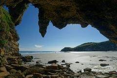 View from a cave with stalactites, west coast, New Zealand. View from a cave with stalactites, to a west coast beach and a couple walking,, New Zealand stock photos