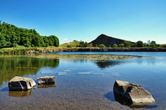 View of Cawfields Quarry, Hadrians Wall. Cawfield Quarry by Hadrians Wall, Northumberland, with rocks in the foreground on a summer day Stock Image