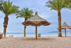 Stormy weather at the gulf of Eilat - famous resort city in Israel. View on the central sand beach of Eilat - famous resort city and southernmost marine port in Stock Photos