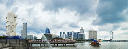 View of central Singapore with Merlion fountain. Singapore, Singapore - January 16, 2018: Merlion fountain spouts water in front of the Marina Bay towers Royalty Free Stock Photos