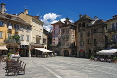 View on central square of Domodossola, Piedmont, Italy. View on central square (Piazza del Mercato) of Domodossola with medieval buildings and street cafes under Royalty Free Stock Images