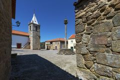 View of the central square of the historic village of Castelo Mendo, in Portugal, with a church and pillory. Concept for travel in Portugal stock image