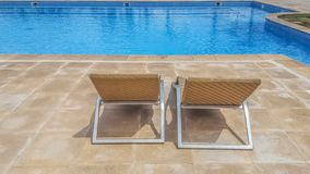View of chair loungers in resort hotel with pool of transparent and crystal clear water. Recreation, blue, vacation, relax, summer, sun, bath, leisure, beach royalty free stock image
