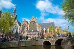 View on the channel with the Old church and tourists on the street in Amsterdam royalty free stock image