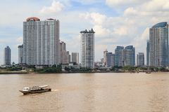 View of chao phraya river with Bangkok Metropolis City Background. And Express Taxi Boat Foreground, Cityscape under Beautiful Sky Royalty Free Stock Image