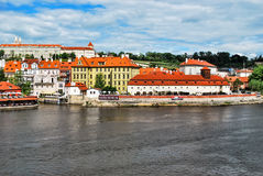 View of the Charles Bridge with a view of the red roofs and Kafka Museum in Prague against the blue sky with clouds. Royalty Free Stock Photography