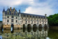 View of Chateau de Chenonceau and river. Beautiful medieval castle Chateau de Chenonceau in France and river flowing in its arches stock photography