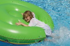 View of a boy 7 jumping from the side of the pool onto a green inflatable bed in the water. stock photography