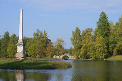 View of the Chesme obelisk and the Humped bridge september day. Gatchina Royalty Free Stock Photo
