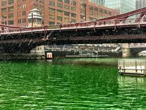 View of Chicago River after being dyed green for St. Patrick& x27;s Day, with snow showers coming down Royalty Free Stock Image