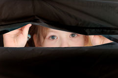 View from childhood. Child face looking over the hole in a black matherial Royalty Free Stock Photo