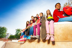 View of children diversity with skateboards. And helmet sitting on stoned ground at autumn day time together Royalty Free Stock Images