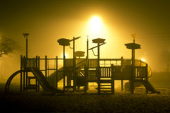 The view on the children playground in foggy and mysterious park. Royalty Free Stock Image