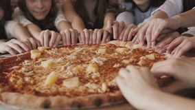 View of children`s fingers moving synchronously and fast to pizza in a centre stock video
