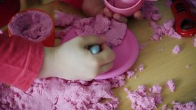 View of children`s hands playing with kinetic sand on the table. Two lovely girls sit at the table and play with pink kinetic sand stock video