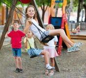 View on children swinging together on children`s playground. View on happy frisky children swinging together on children`s playground in town stock photo