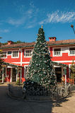 View of Christmas tree and wooden house on sunny day in Penedo. Penedo, Brazil - January 18, 2015. View of Christmas tree and wooden house on sunny day in Royalty Free Stock Photos