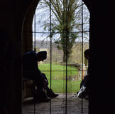 View from a church door. Two walkers resting in a church doorway silhouetted against the background taken from inside the church Royalty Free Stock Images