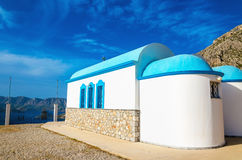 A view of a church with iconic blue roof and see. In the background on Greek island, Kalymnos, Greece Royalty Free Stock Photo