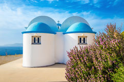 A view of a church with iconic blue roof and see in the. Background on Greek island, Kalymnos, Greece Stock Image